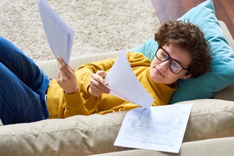 Junge Frau liegt auf Sofa und schaut durch Dokumente