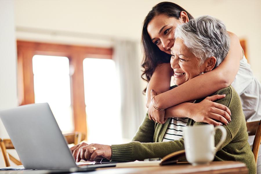 Frau sitzt am Computer und wird von jüngerer Frau umarmt