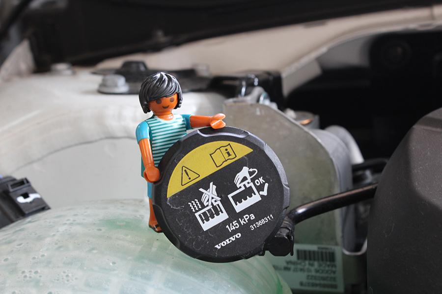 Playmobilmännchen öffnet Deckel des Kühlwasserbehälters am Auto
