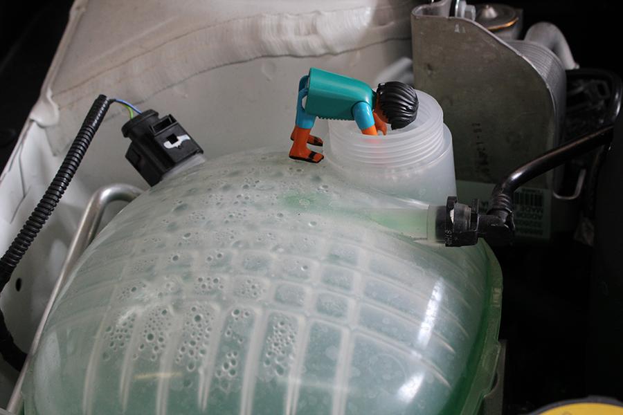 Playmobilmännchen kopfüber in der Öffnung, wo im Auto Kühlflüssigkeit eingefüllt wird