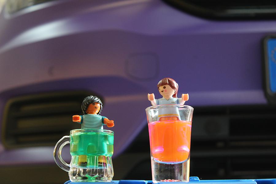 Zwei Schnappsgläser, jeweils mit grüner und rosa Kühlflüssigkeit befüllt, in der Playmobilmännchen baden