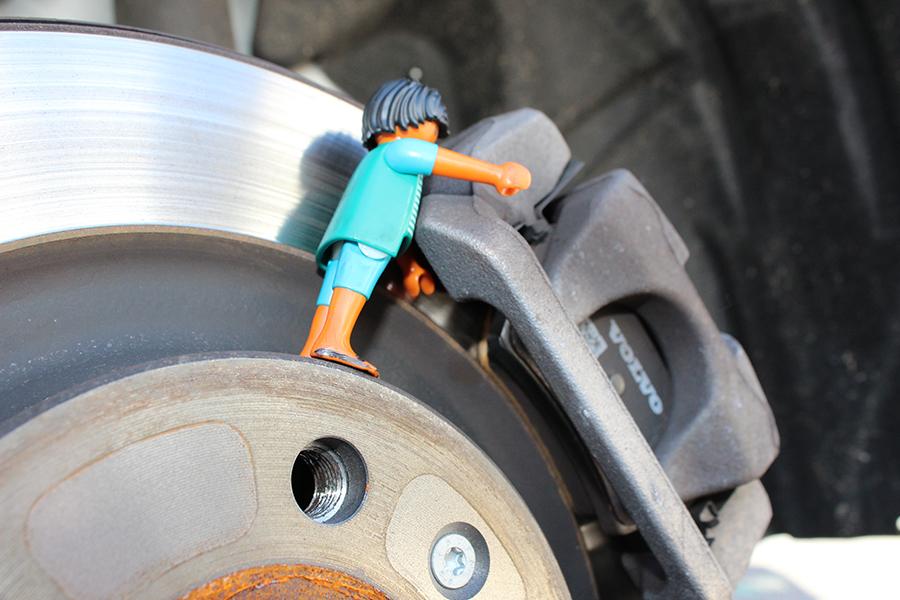 Playmobilmännchen steht auf Autoreifen an der Bremse