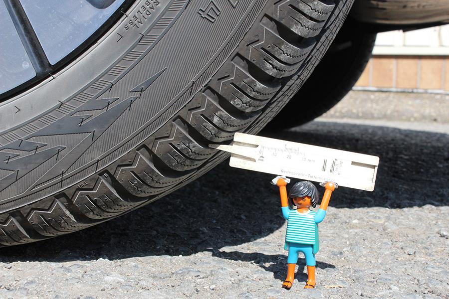 Playmobilemännchen das mit einem Messgerät die Profiltiefe eines Reifen misst