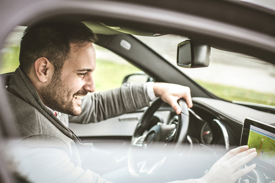 Dunkelhaariger Mann am Steuer seines Autos