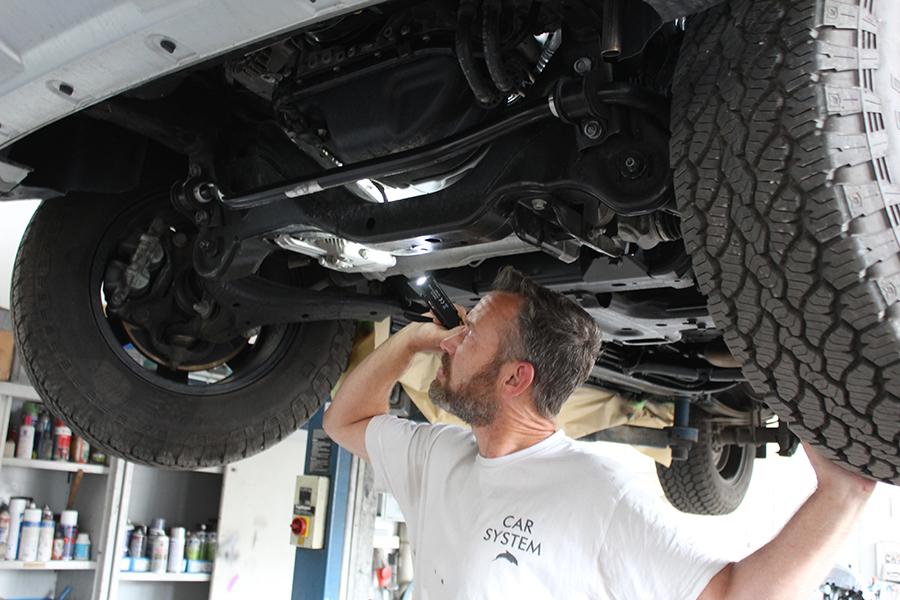 Automechatroniker unter einem Auto auf der Hebebühne