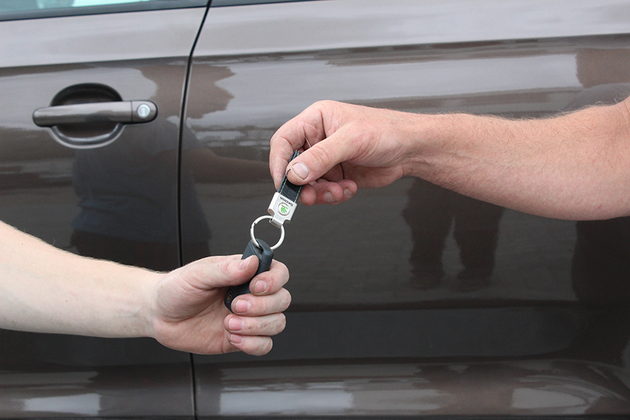 Zwei Hände vor einem Auto die einen Kfz-Schlüssel weiterreichen