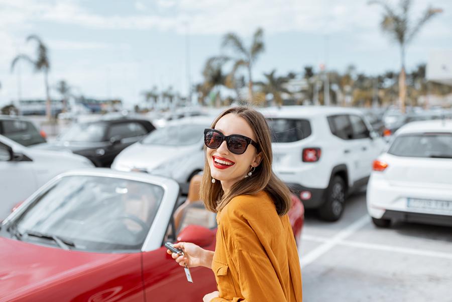 Junge Frau mit Sonnenbrille mit Autoschlüssel in der Hand auf einem Parkplatz